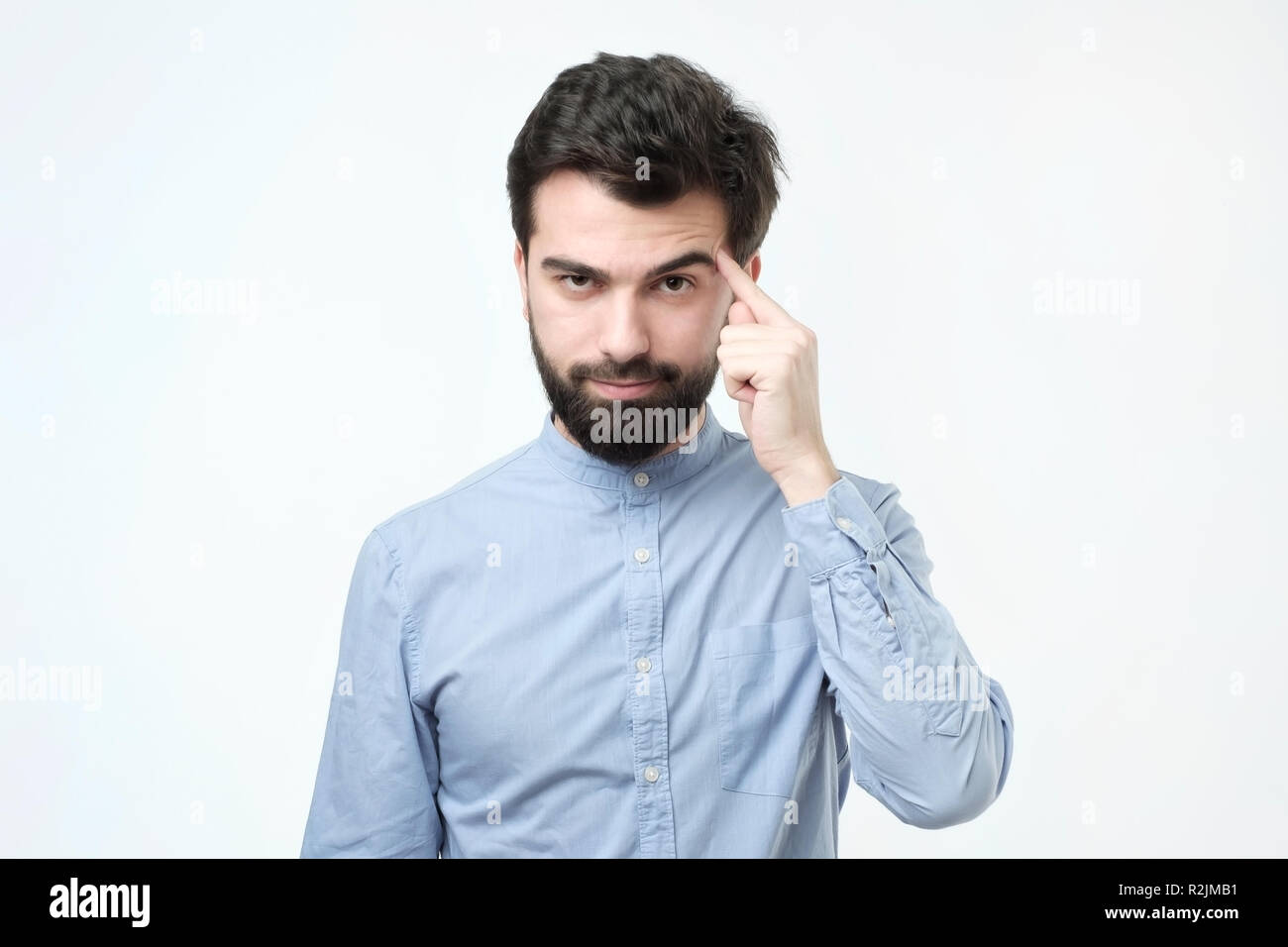 Let me think. Serious hispanic man with beard, keeps index finger on temple, recollect something in mind - Stock Image
