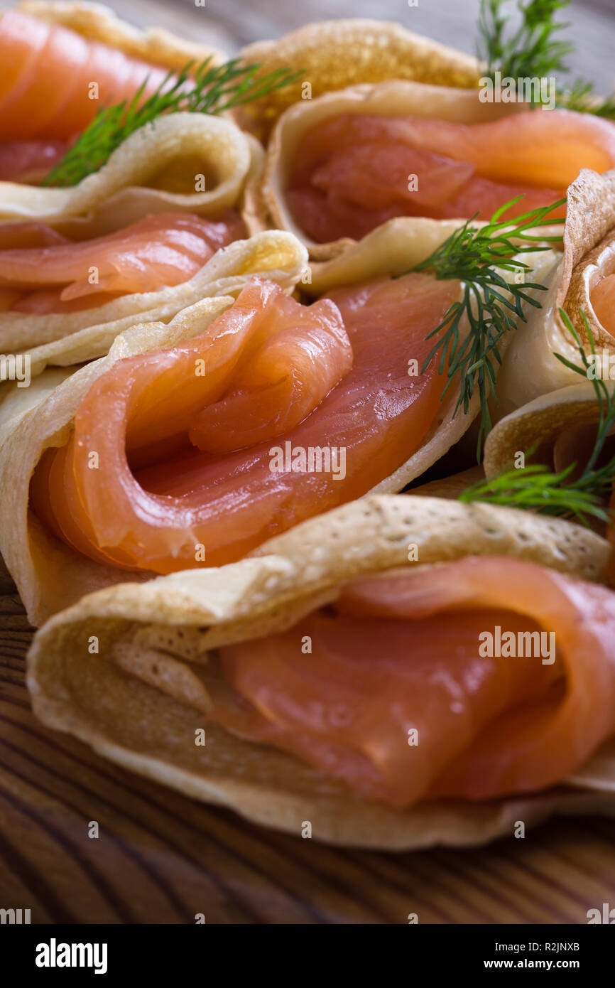 Smoked salmon appetizer, stuffed crepes on wooden board close up - Stock Image