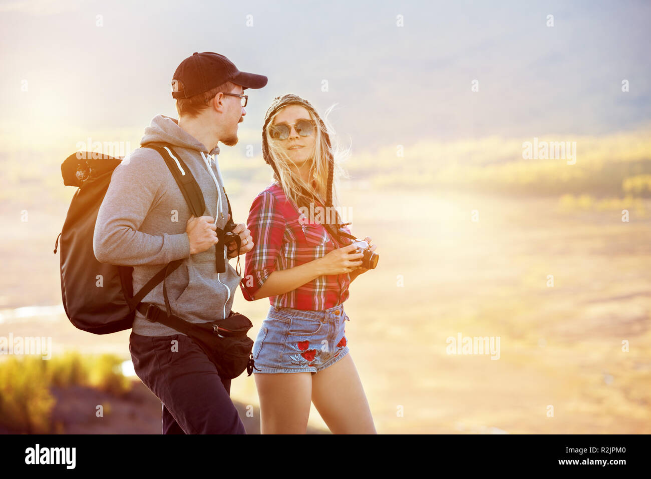 Two young tourists stands and speaks. Travel or trekking concept with couple Stock Photo