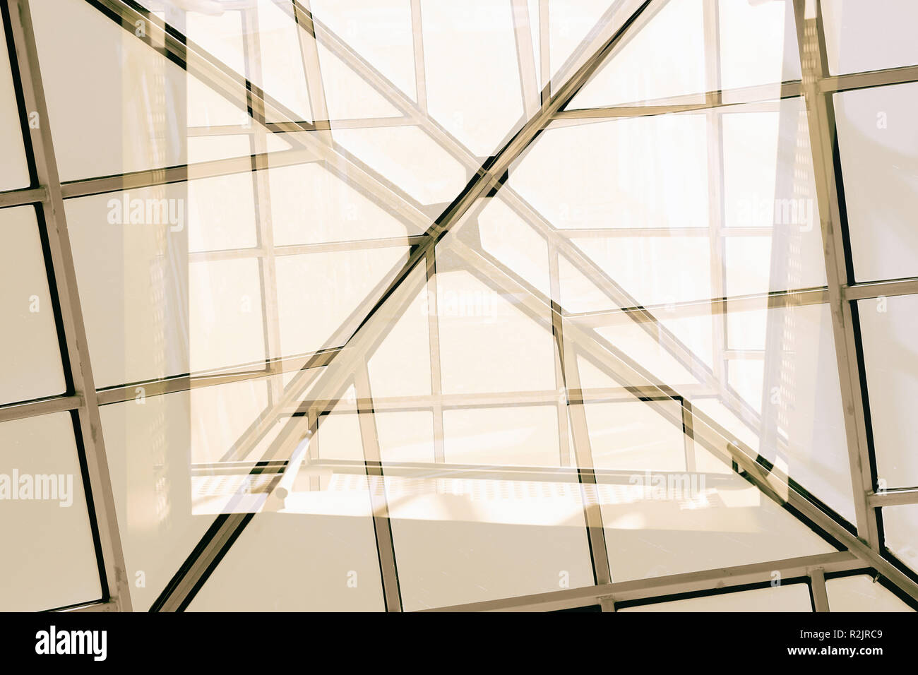 Roof and glass construction of a staircase with a square spiral staircase and railing - Stock Image