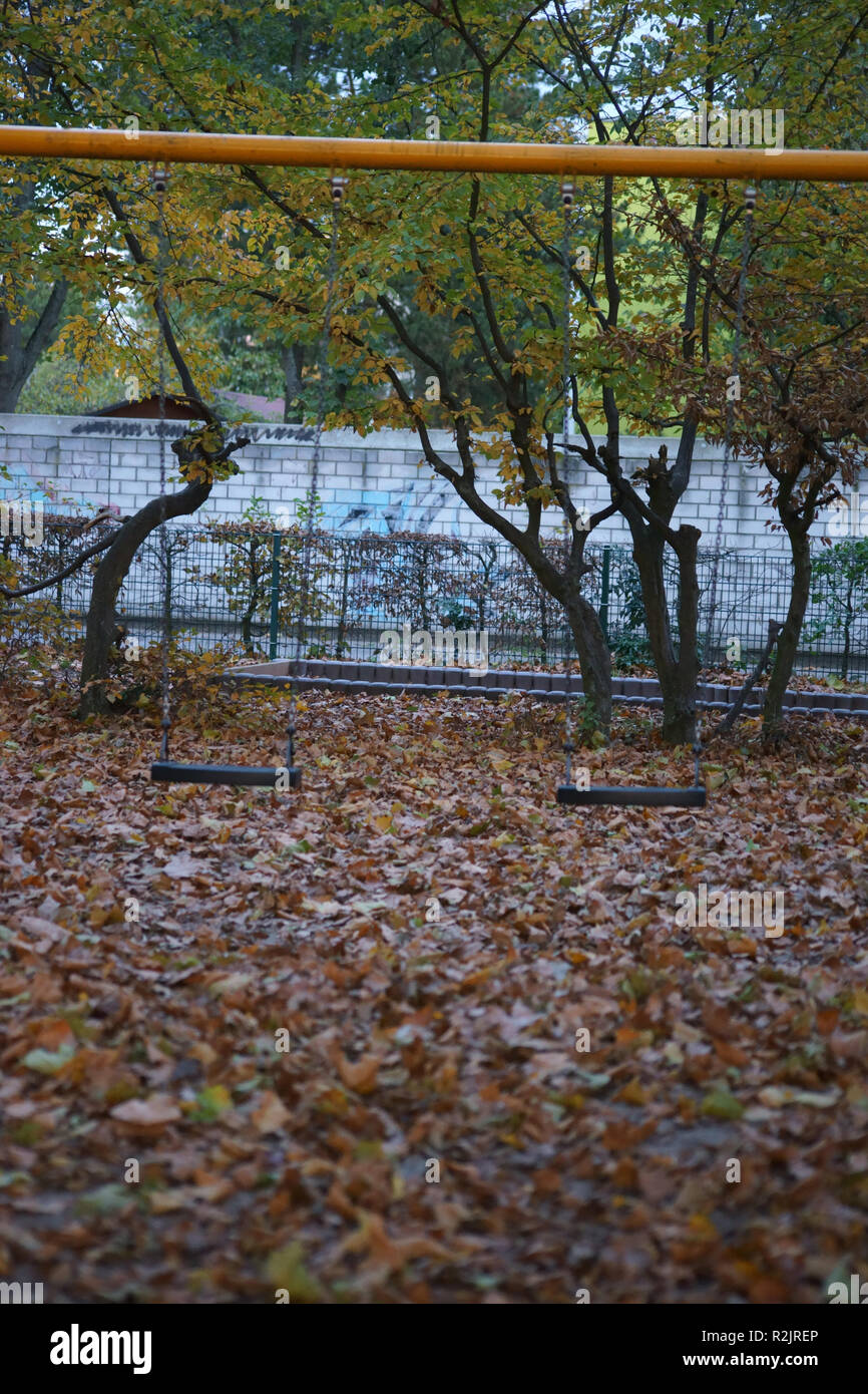 An unused playground in the city in autumn with a swing, - Stock Image