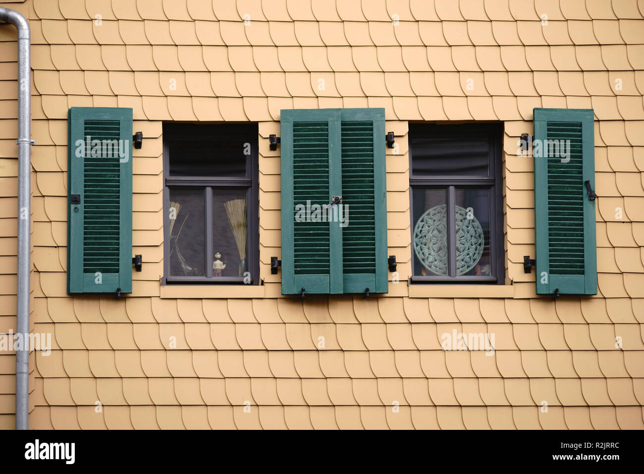 Open shutters on a striking facade of yellow shingles, - Stock Image