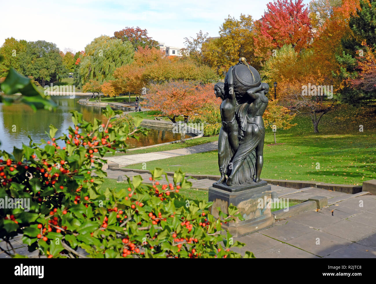 The bronze statue, Night passing the Earth to Day, by Frank Jirouch is surrounded by colorful autumn foliage in Wade Park in Cleveland, Ohio, USA. - Stock Image