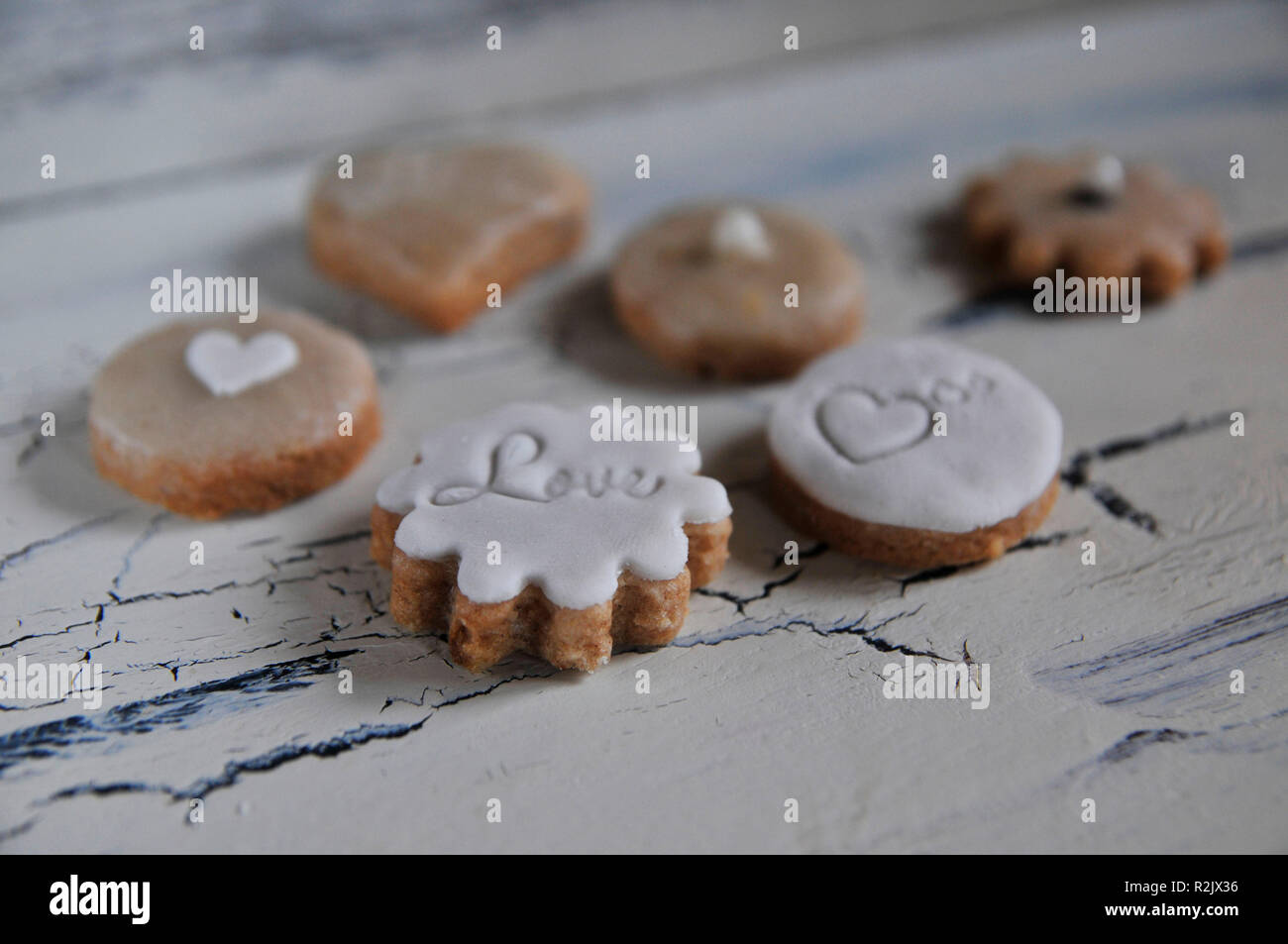 Cookies with heart and Love writing in close-up on white shabby chic background - Stock Image