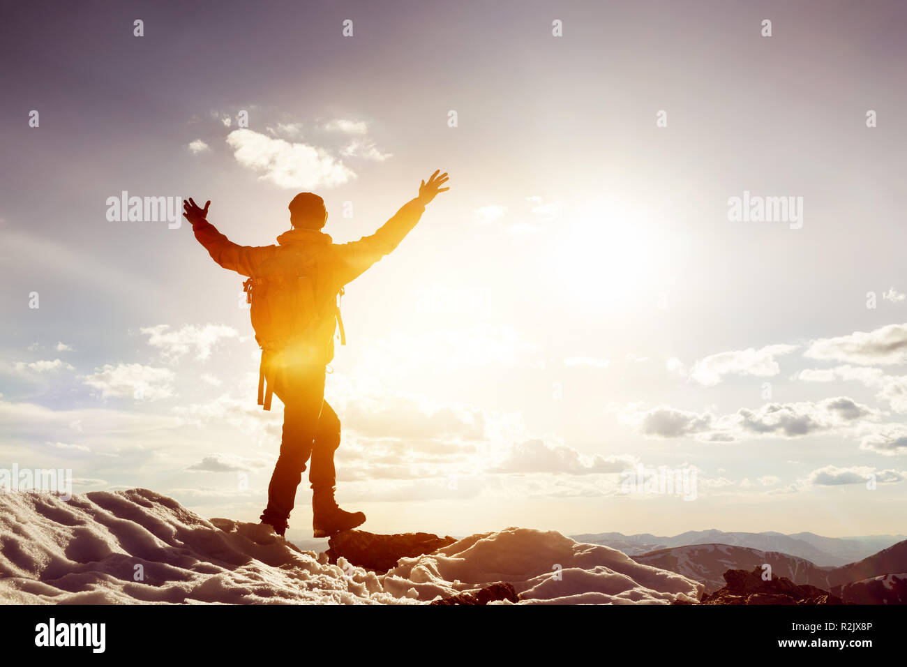 Man stands in winner pose with raised arms on mountain top. Trekking or win concept Stock Photo