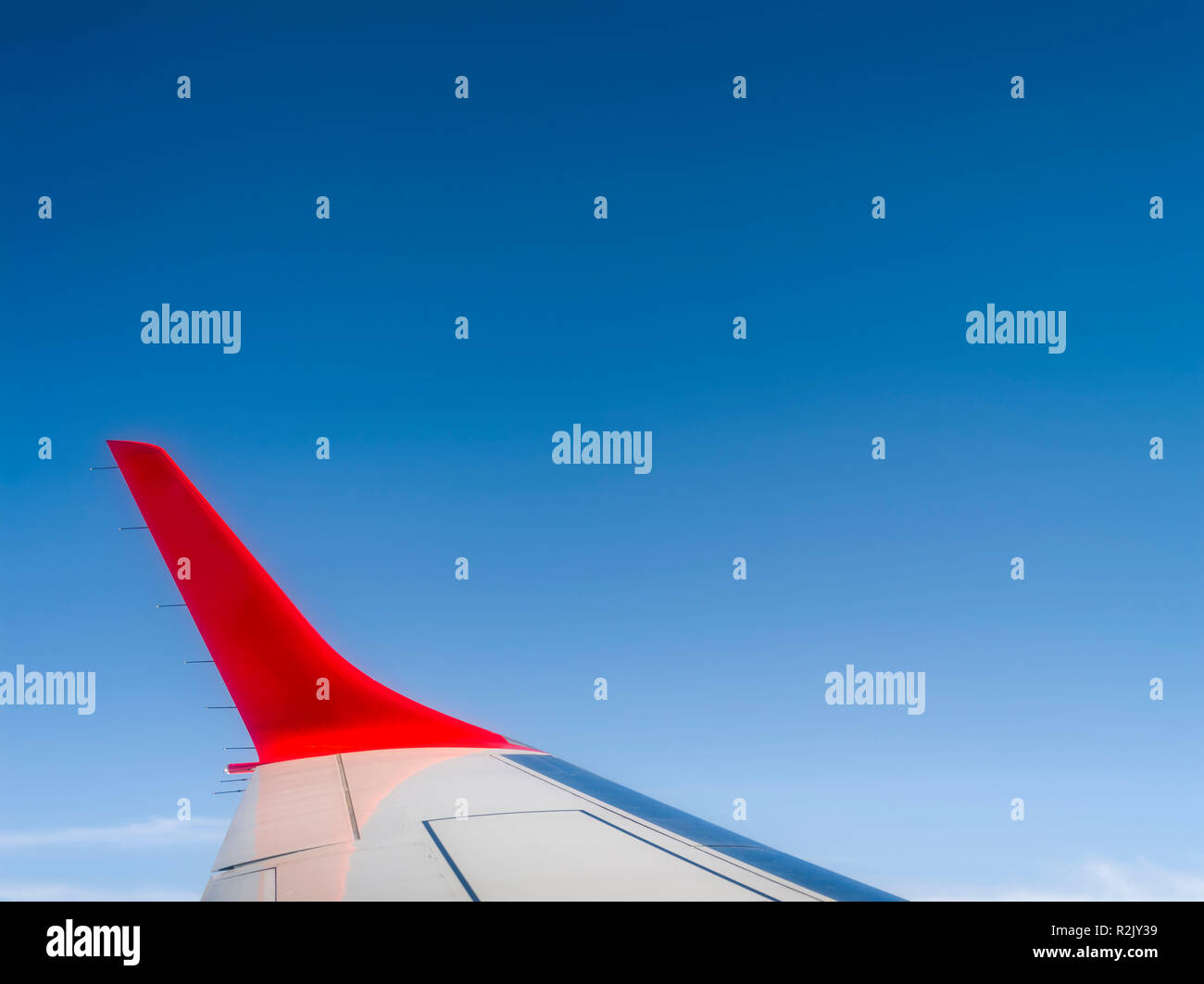 Red wing winglet in front of blue sky - Stock Image