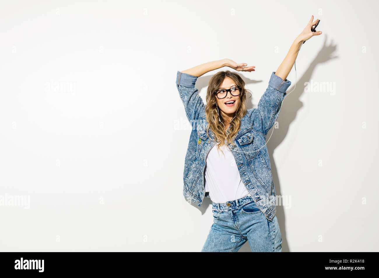 1b30d59d6a04 listen to the music and dance. concept with a young expressive beautiful  woman in retro jeans outfit listening music with headphones and dancing, on  w