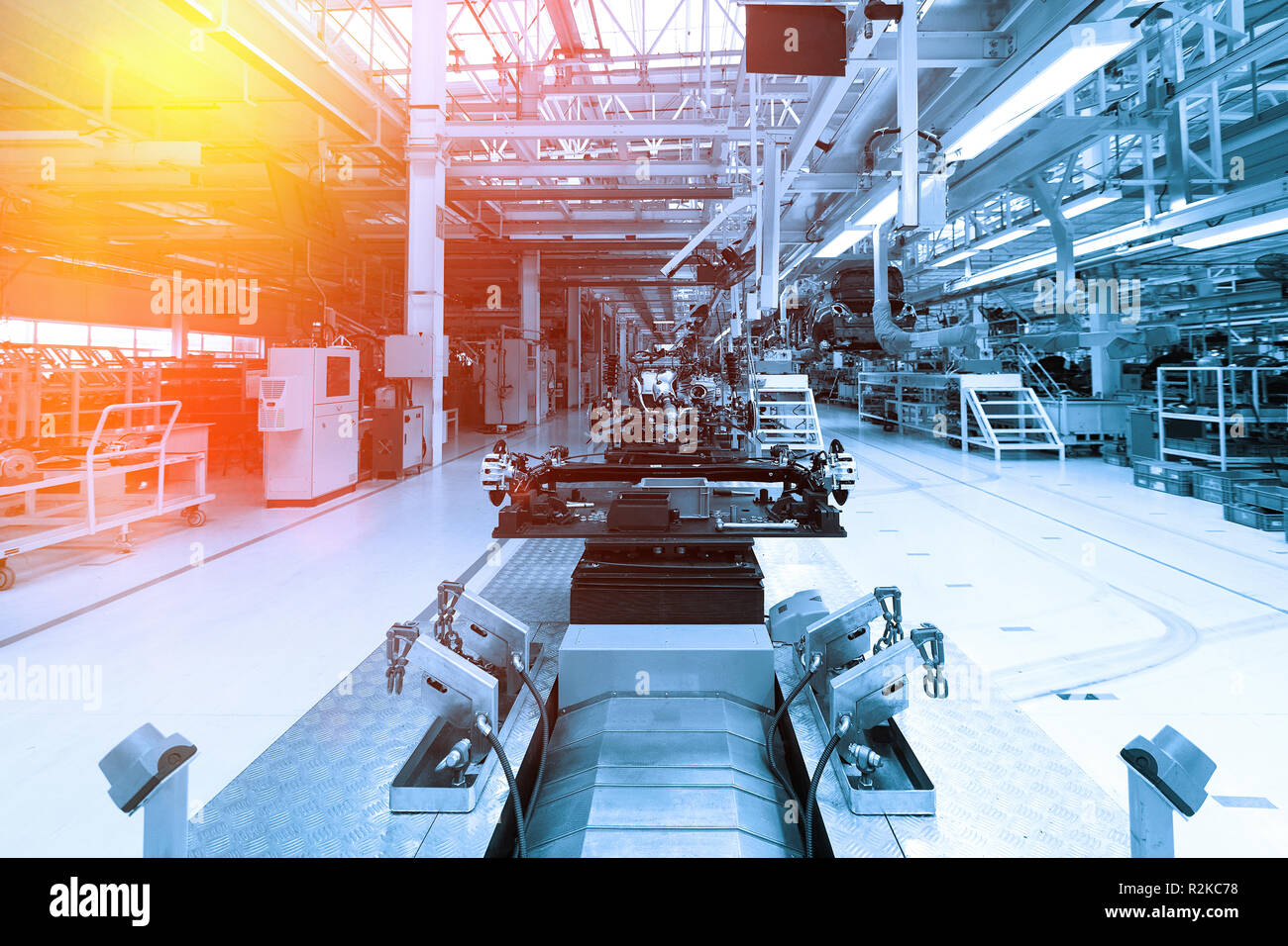 Assembling parts of the car robots. automated build process of cars. Factory for production of cars in blue.Blue tone - Stock Image