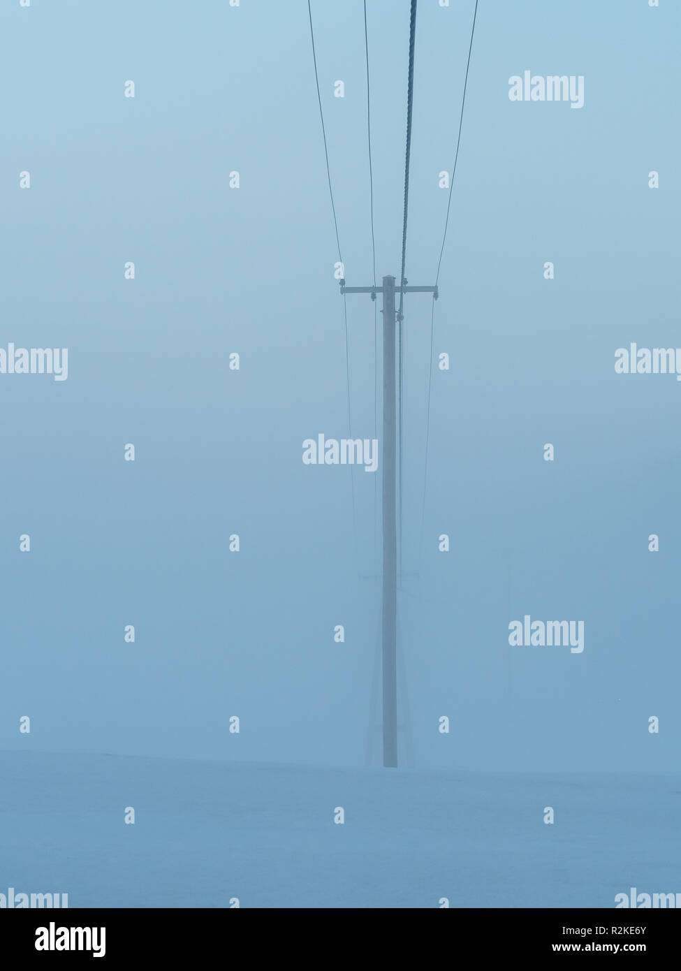 electric power lines on a foggy day - Stock Image
