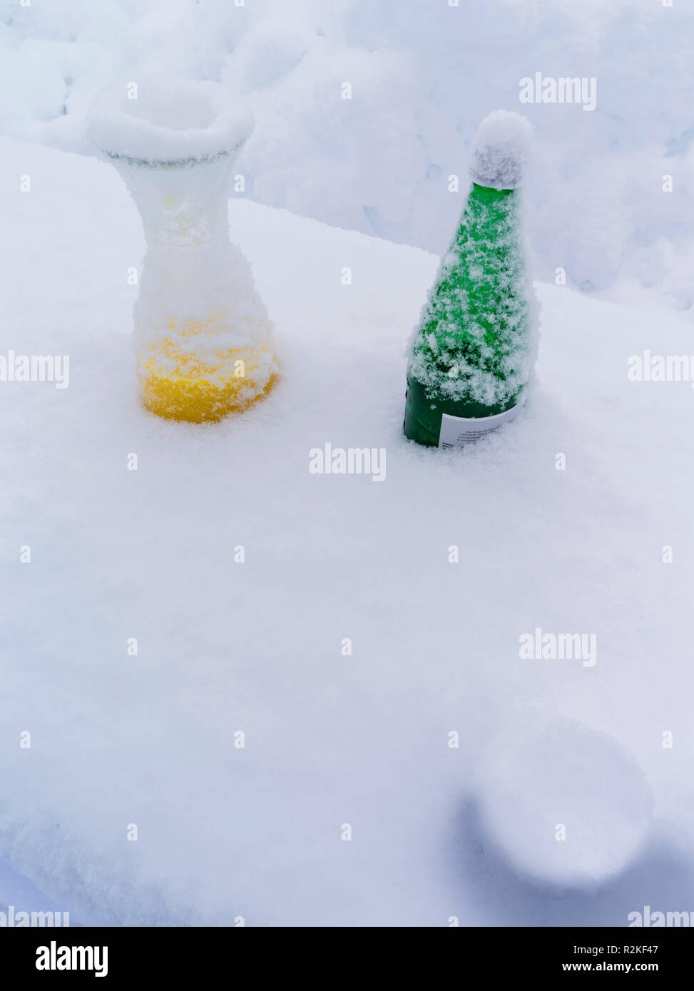 Drink remains in the snow after a party in winter - Stock Image