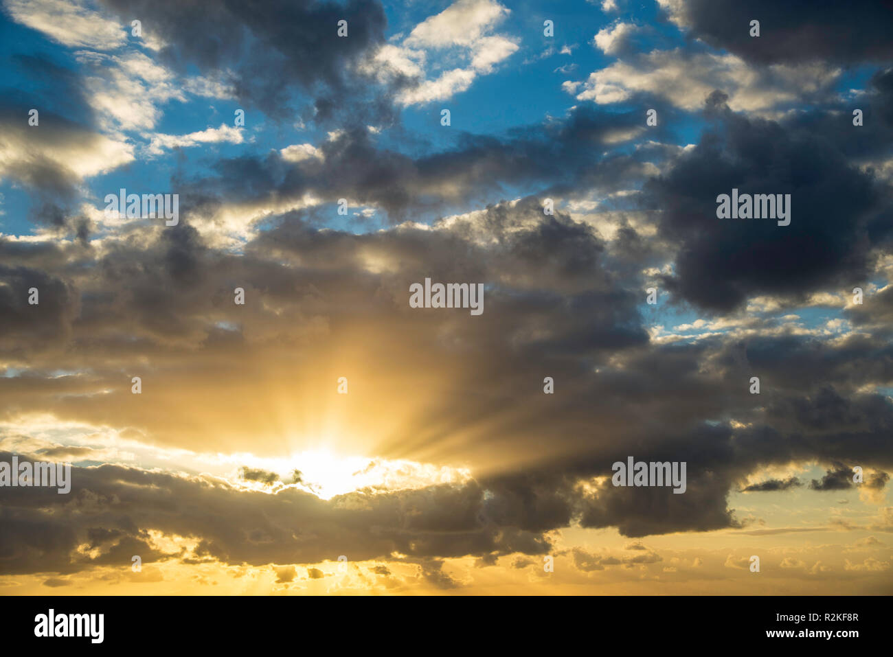 Sunrise in partly cloudy sky. - Stock Image