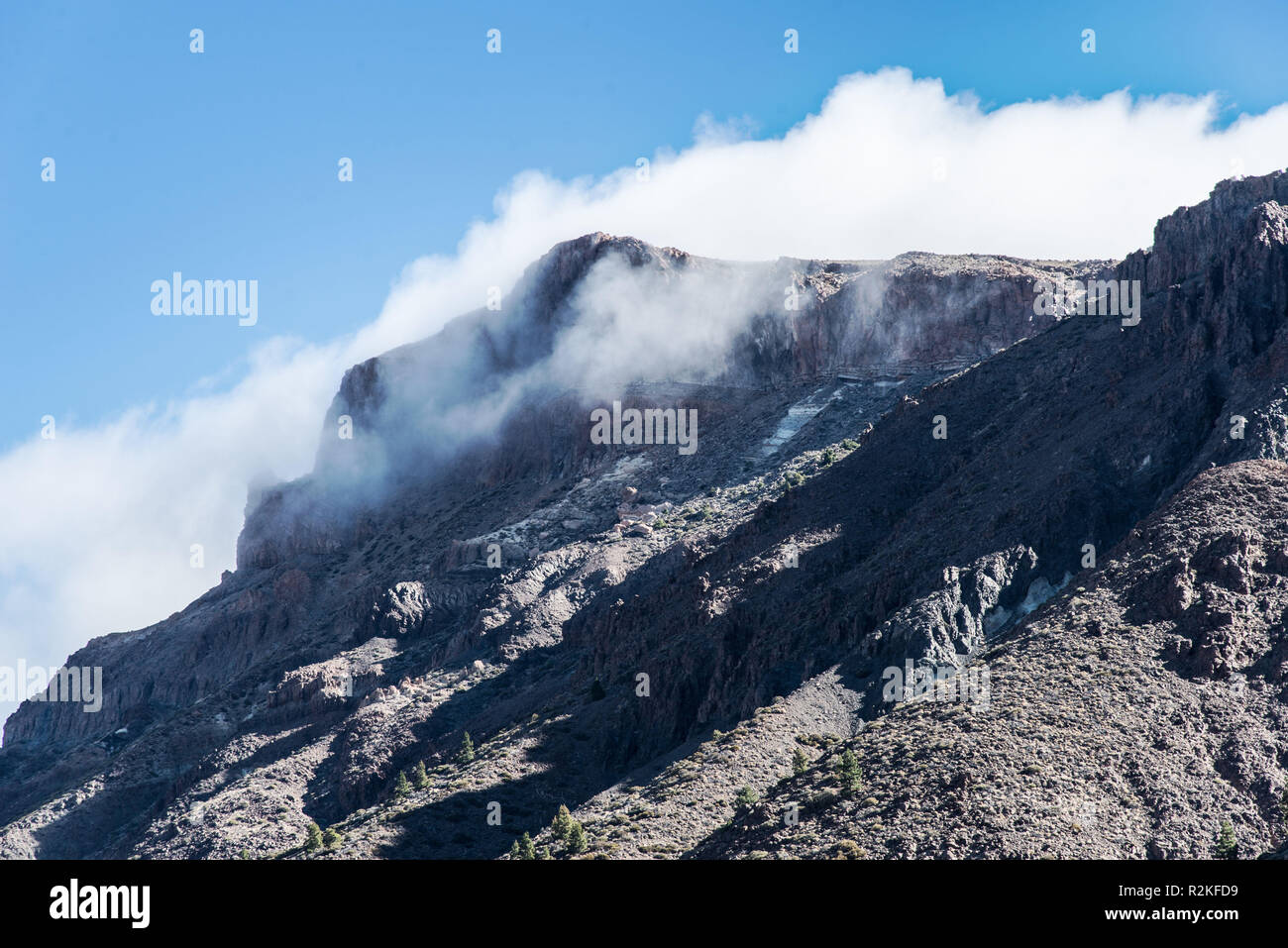 Landscape in El Teide National Park with a partly cloudy mountain peak. - Stock Image
