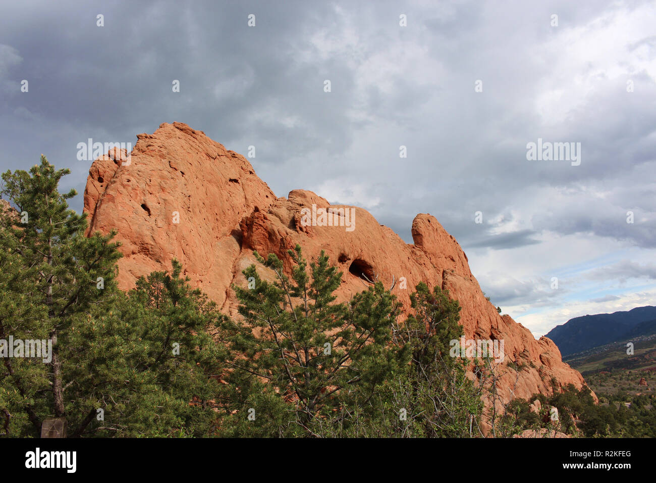 Large rock formation, made of red rock, and pine trees under stormy skies at the Garden of the Gods in Colorado Springs, Colorado, USA - Stock Image