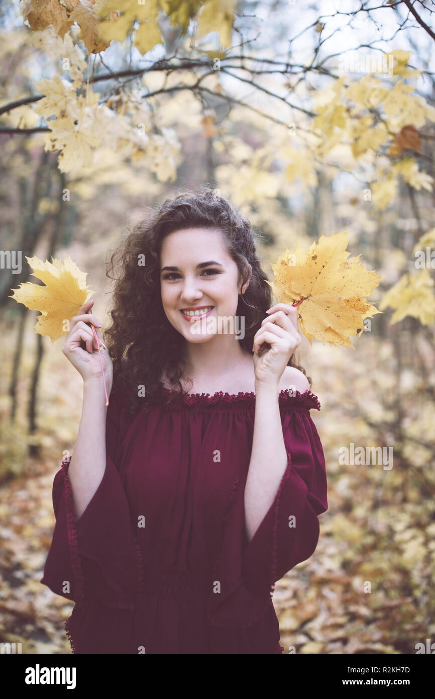 Beautiful girl with curly dark hair in a marron top in an autumn park, smiling at the camera and holding maple leaves Stock Photo