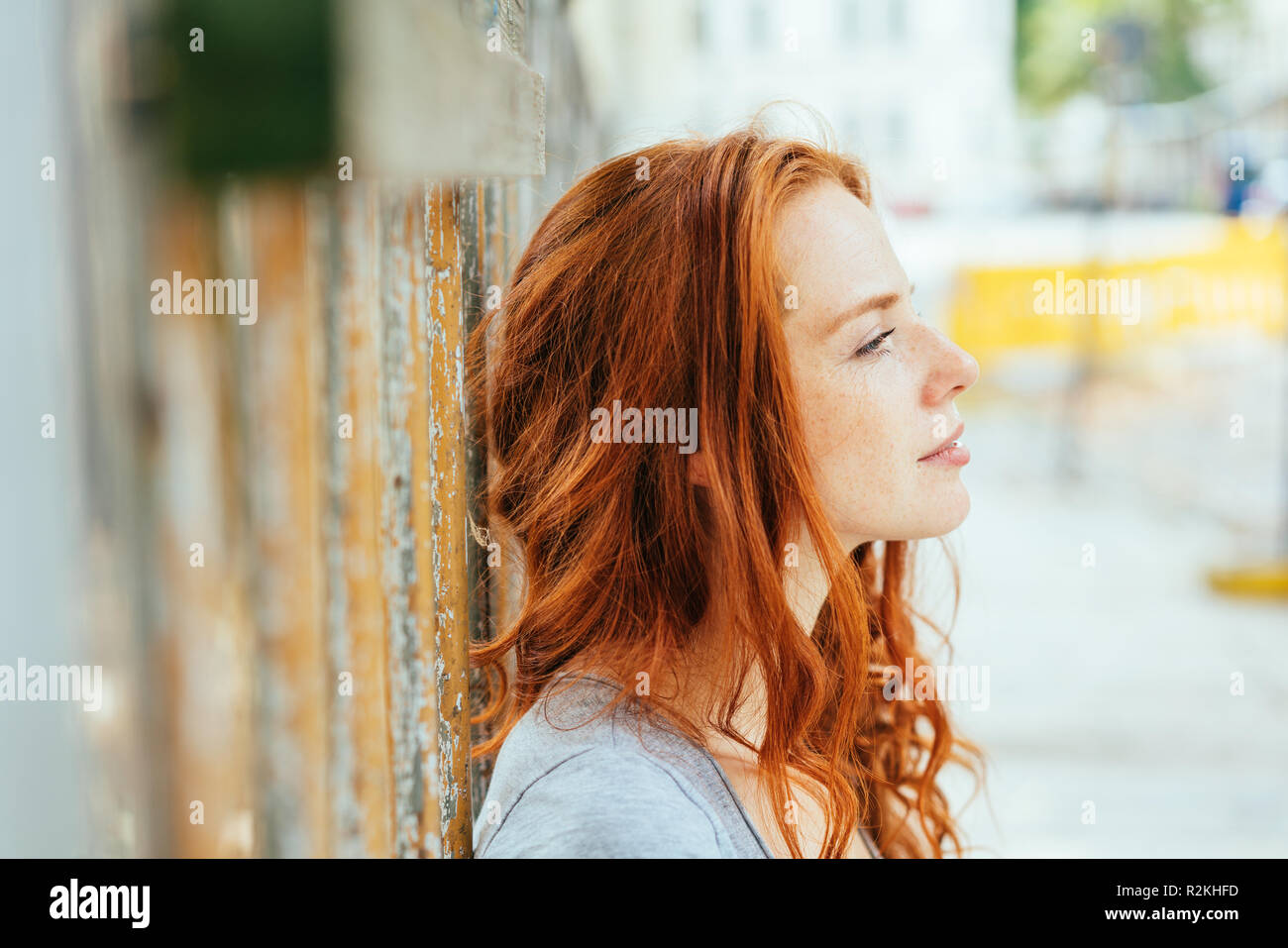 Thoughtful young woman with tousled red hair leaning against an urban wall staring ahead in a close up profile view on a high key background - Stock Image