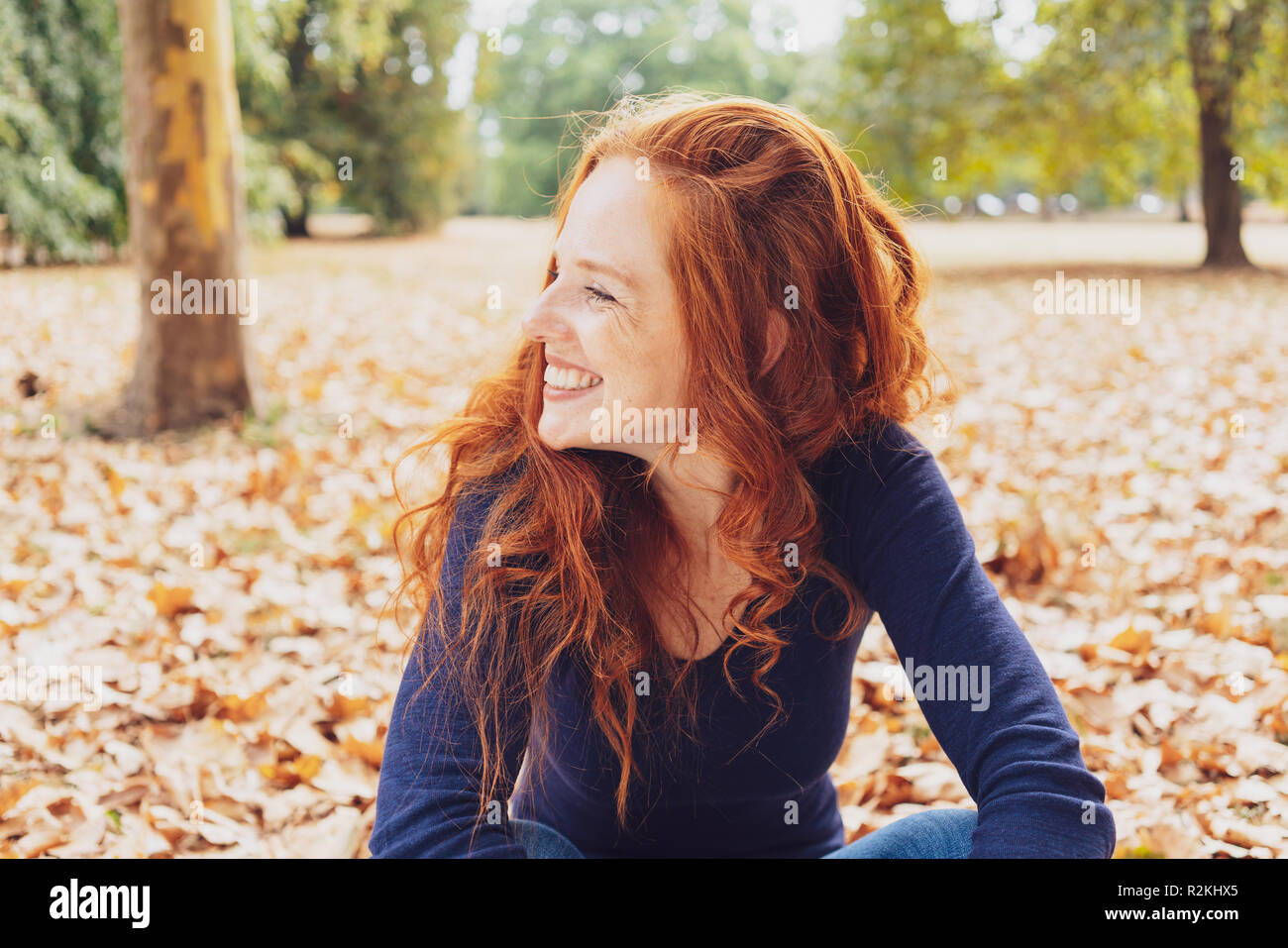 Cute happy young woman with tousled red hair relaxing in a park in autumn sitting amongst the fallen leaves looking to the side with a beaming smile - Stock Image