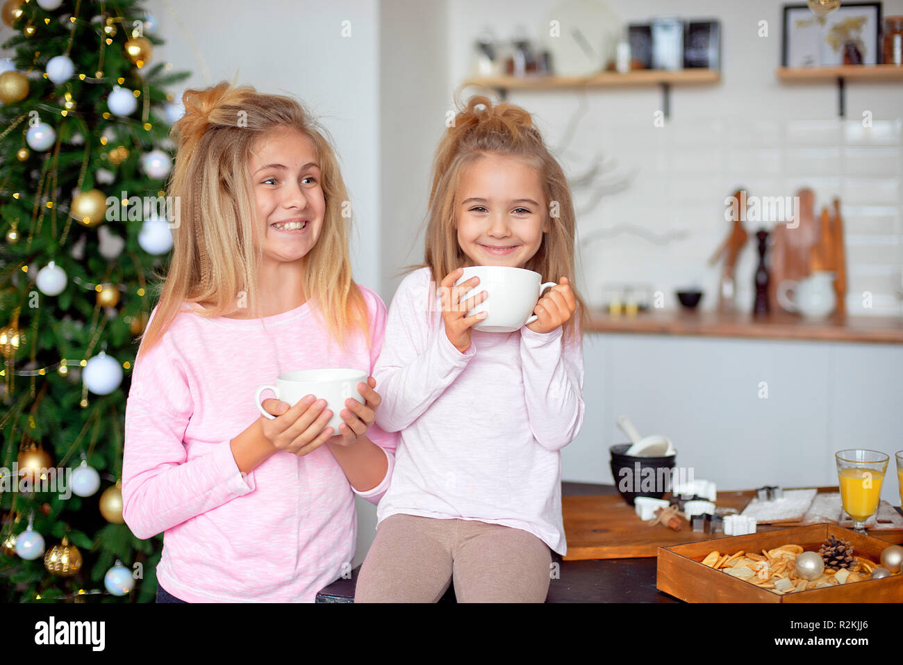Two sisters in their pajamas in the kitchen drinking tea ...