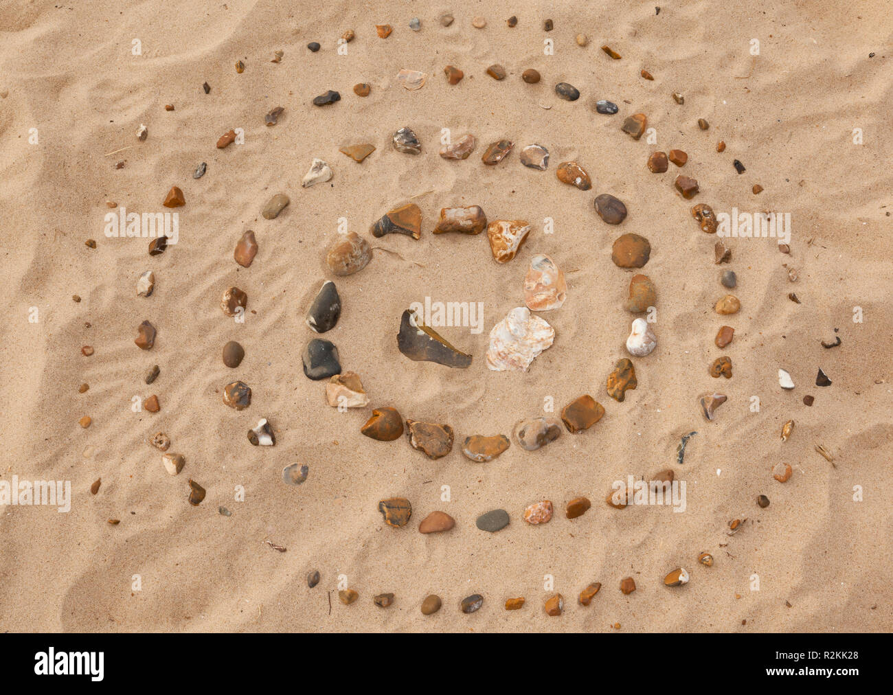 A Labyrinth made of small stones on a sandy beach Stock Photo