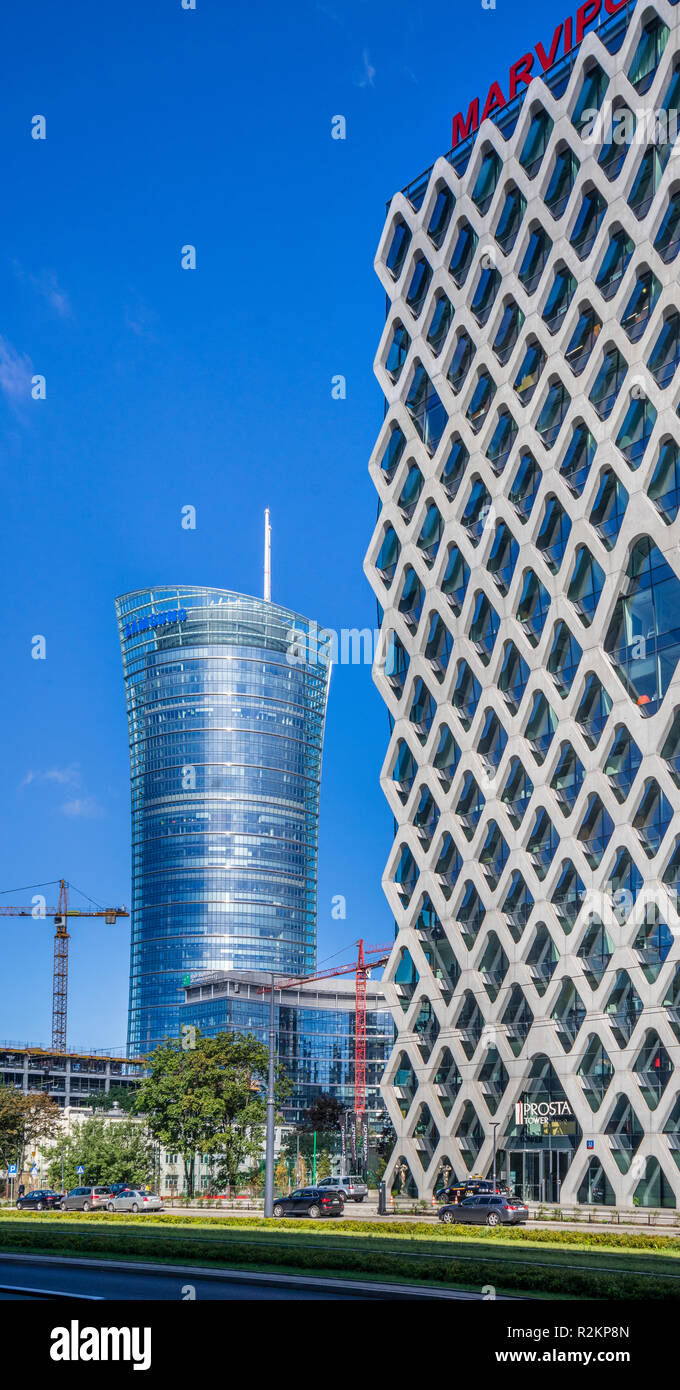 the Prosta Tower office building with its characteristic openwork facade against the backdrop of the Neomodern 49-storey Warsaw Spire with its hyperbo - Stock Image