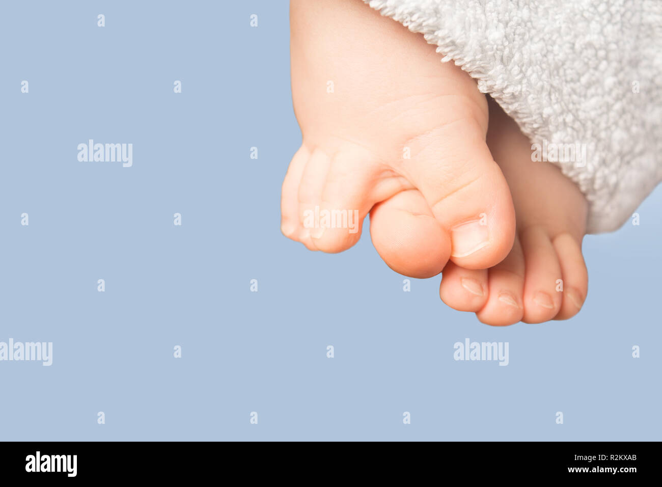 Smal baby feet with blue terry towel on blue background, isolated photo - Stock Image