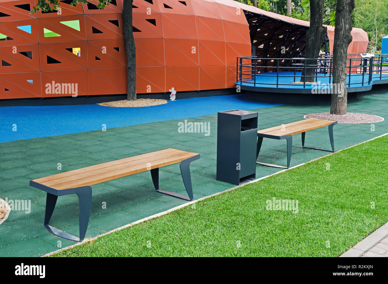 Wooden benches for rest in a childrens inclusive gaming park - Stock Image