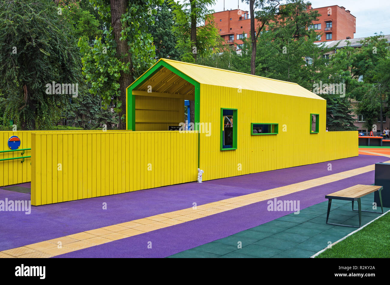 Childrens play house in yellow color in the inclusive municipal park - Stock Image