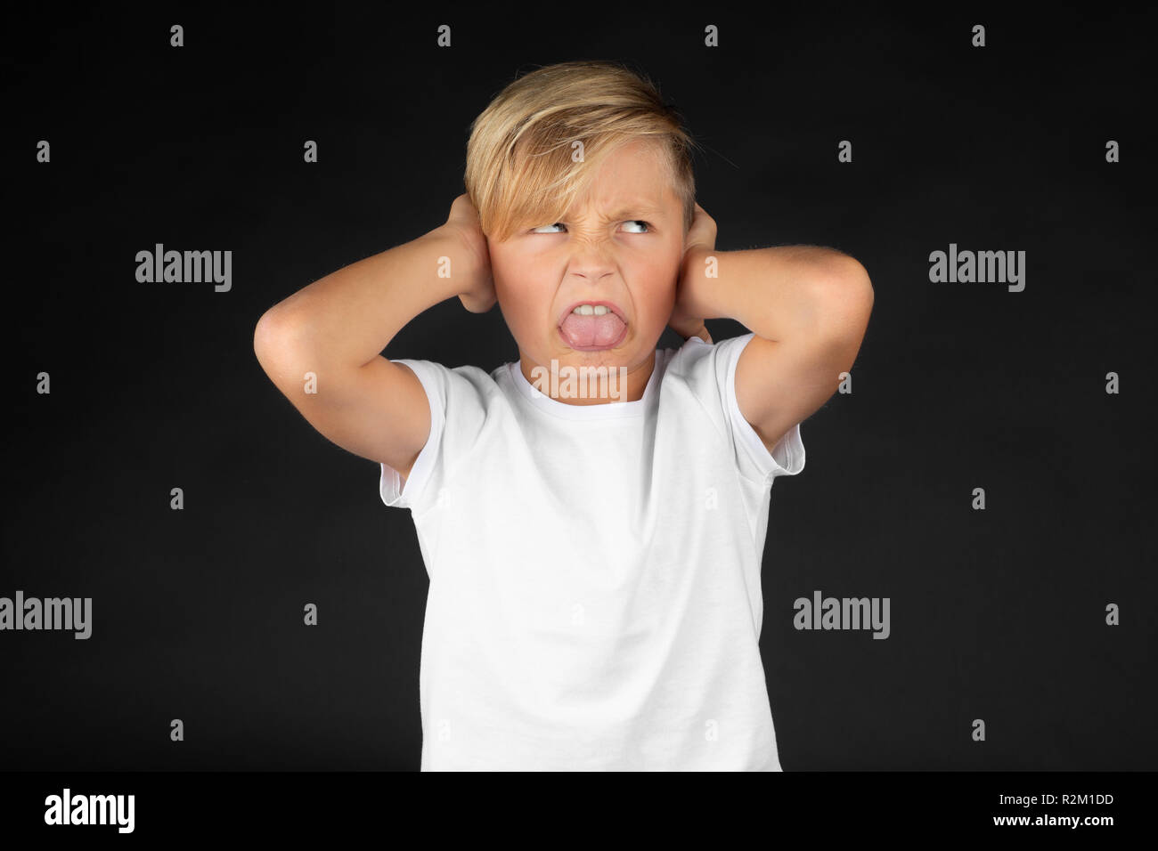 Little blond boy covers his ears and sticks out his tongue - Stock Image