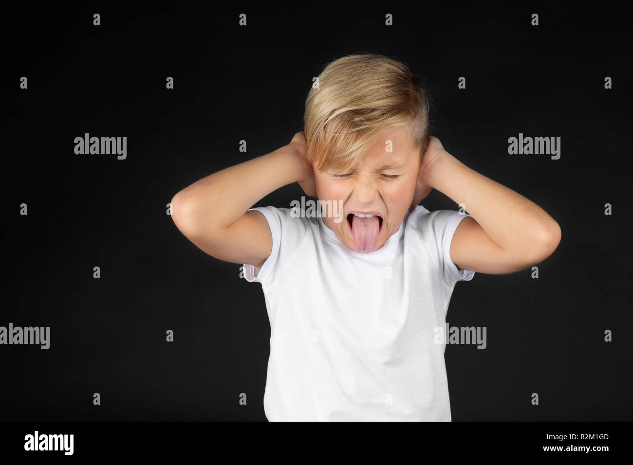 Little blond boy covers his ears and sticks out his tongue Stock Photo