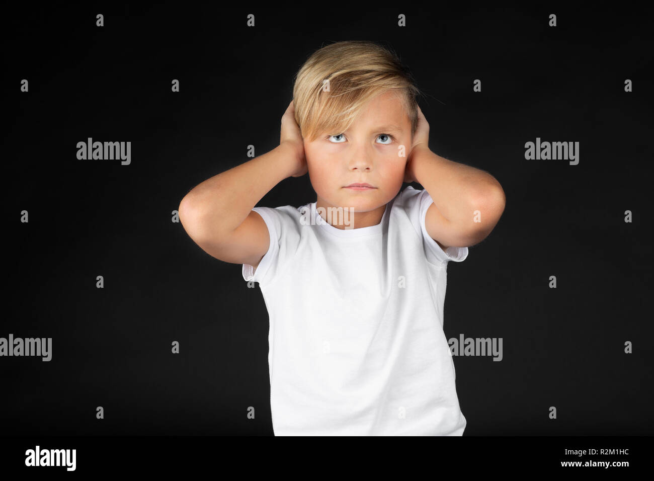 Little blond boy covers his ears - Stock Image