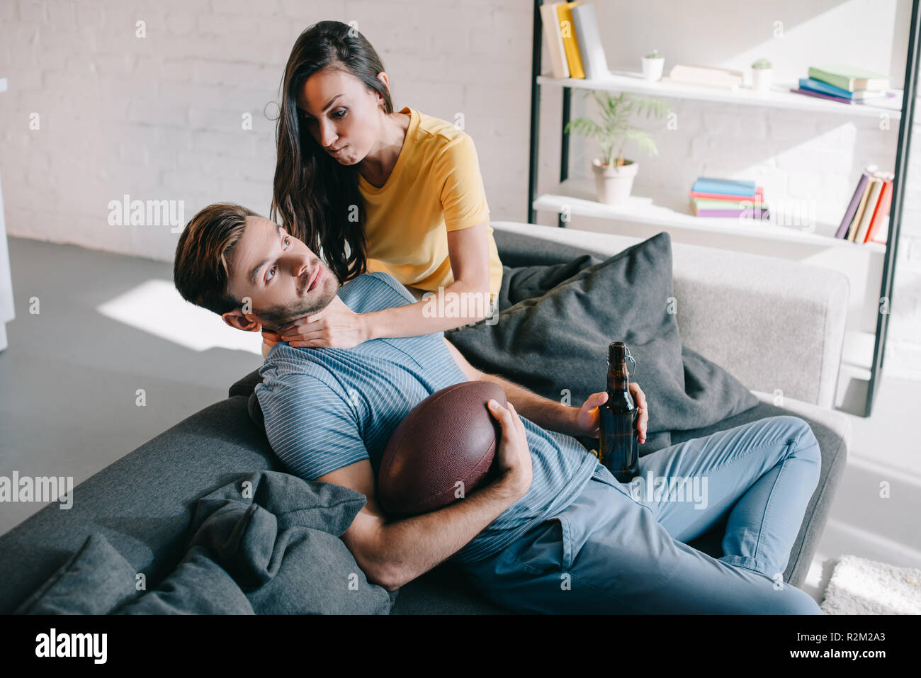 angry woman choking her husband while he watching american football on tv at home - Stock Image
