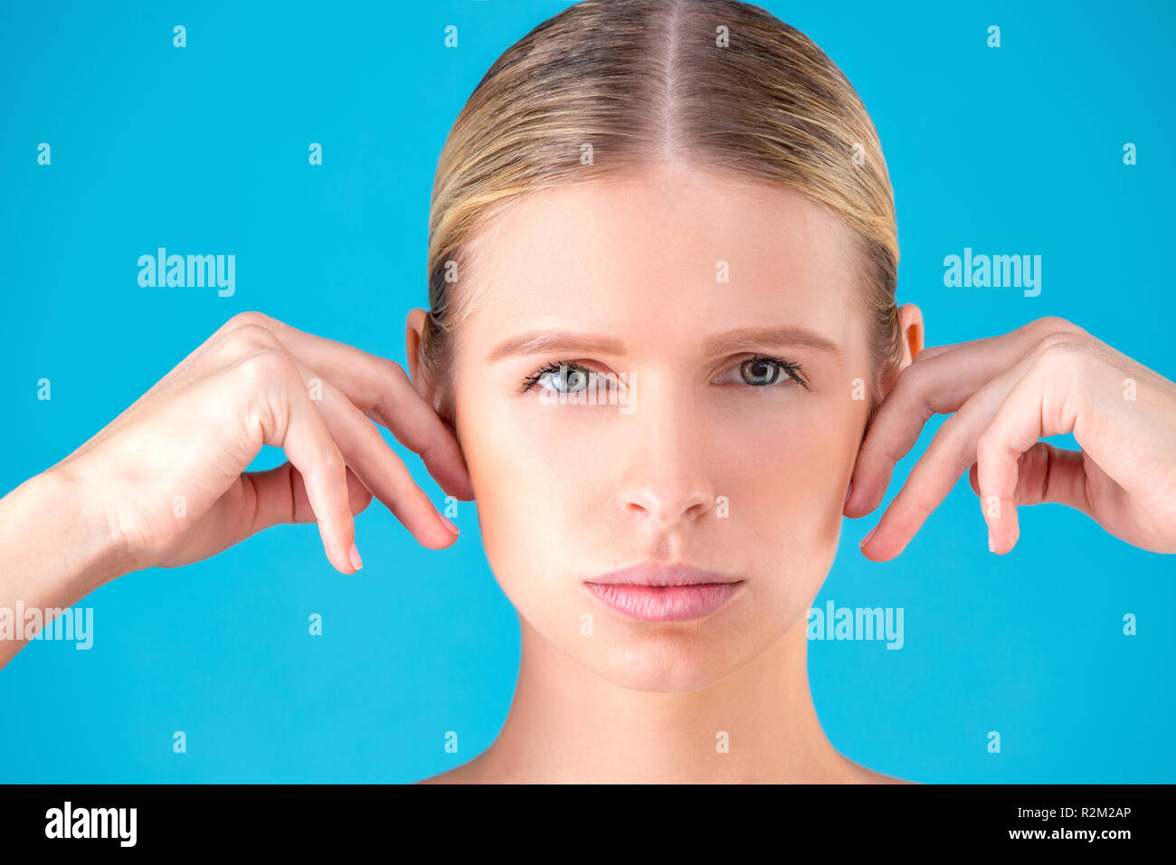 health, spa and beauty concept - clean face of beautiful young woman pointing to her ear - Stock Image