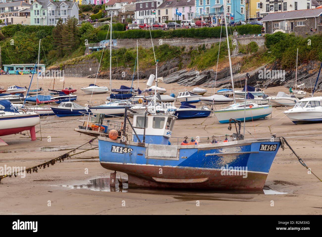 A lobster fishing vessel sits on the sand at low tide, New Quay, wales, Ceredigion - Stock Image