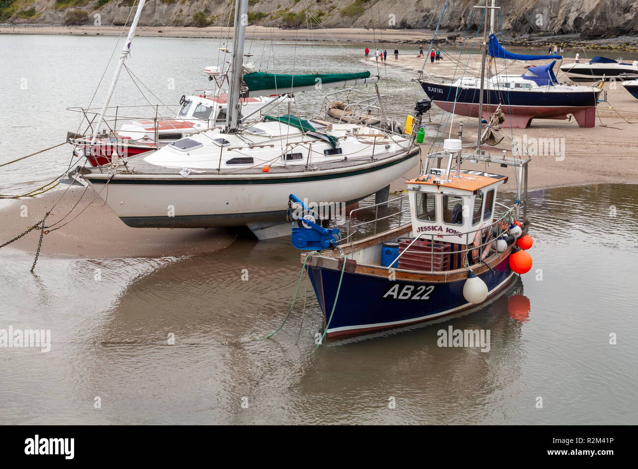 A small lobster fishing vessel is moored up at low tide, New Quay, wales, Ceredigion - Stock Image