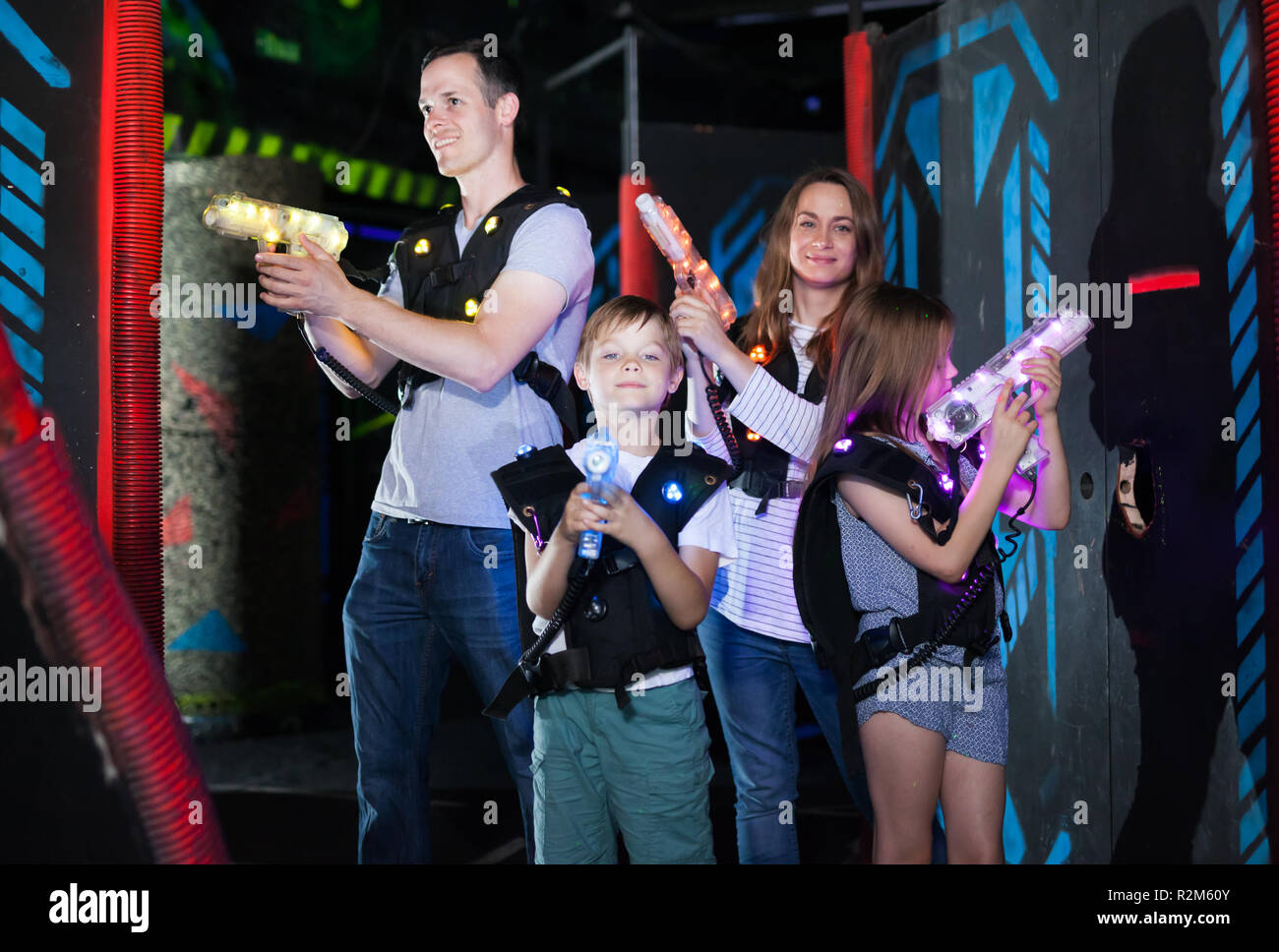 Group of happy kids and adults with laser guns having fun on