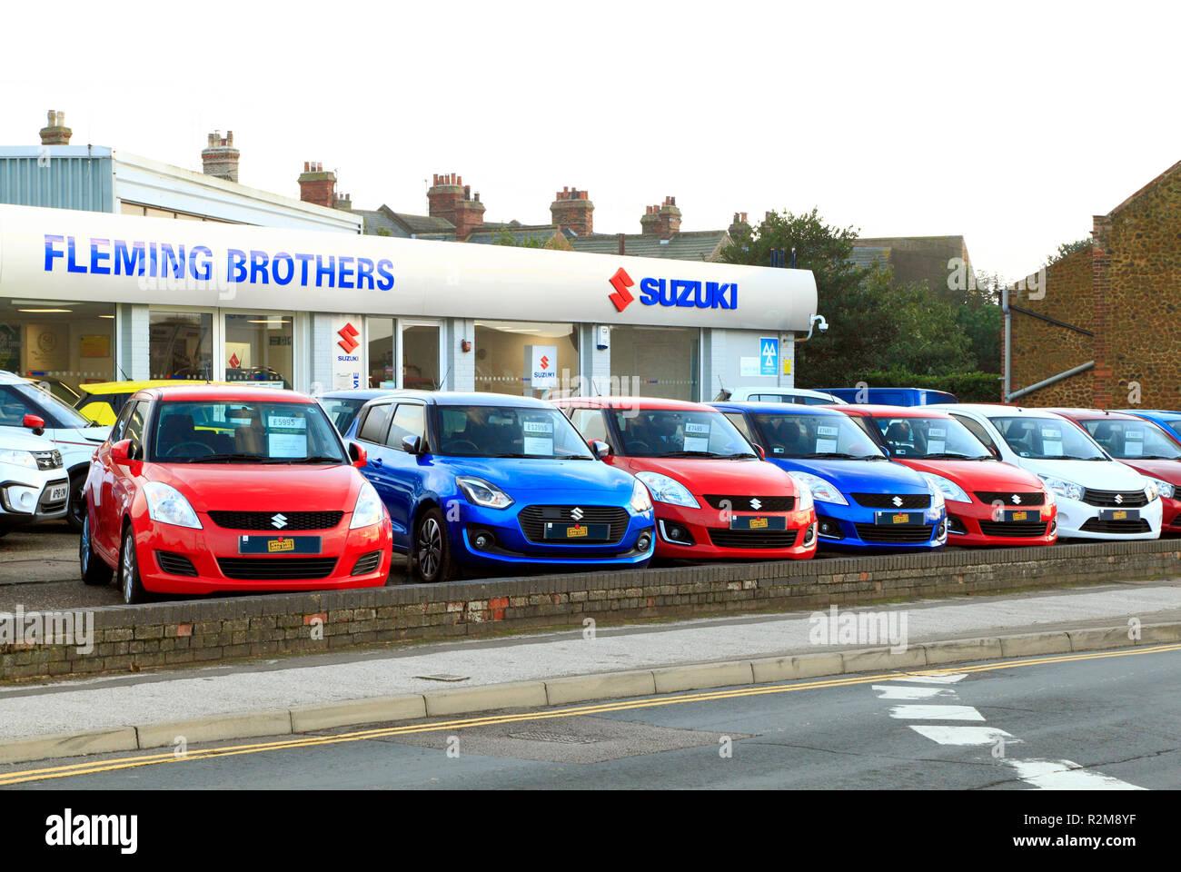 Suzuki, motor cars, Fleming Brothers, forecourt, main dealer, dealership, car, dealer, dealers primary colours,, Hunstanton, Norfolk, UK - Stock Image