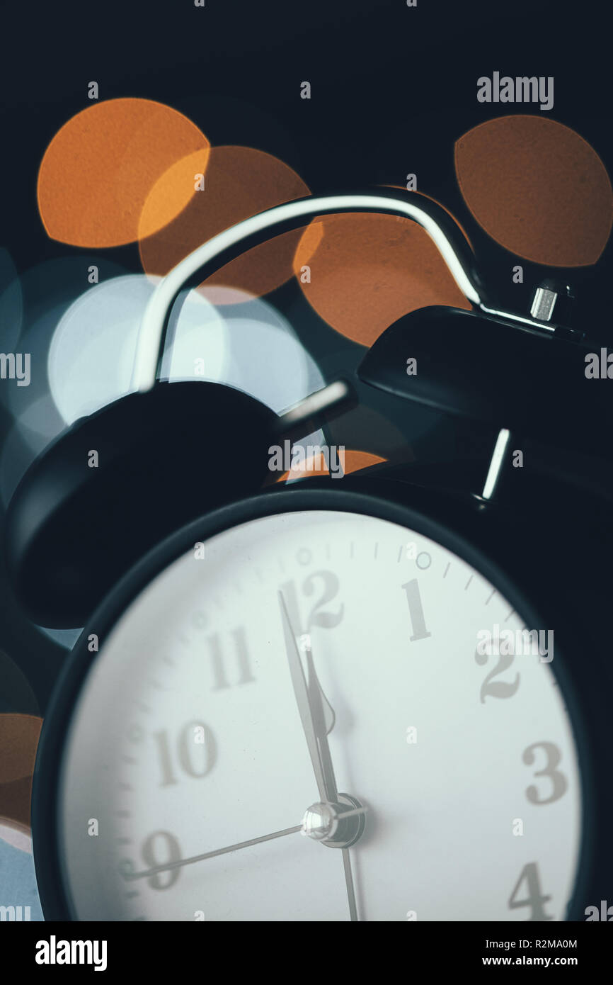 New Year's midnight retro clock face with bokeh lights in background - Stock Image