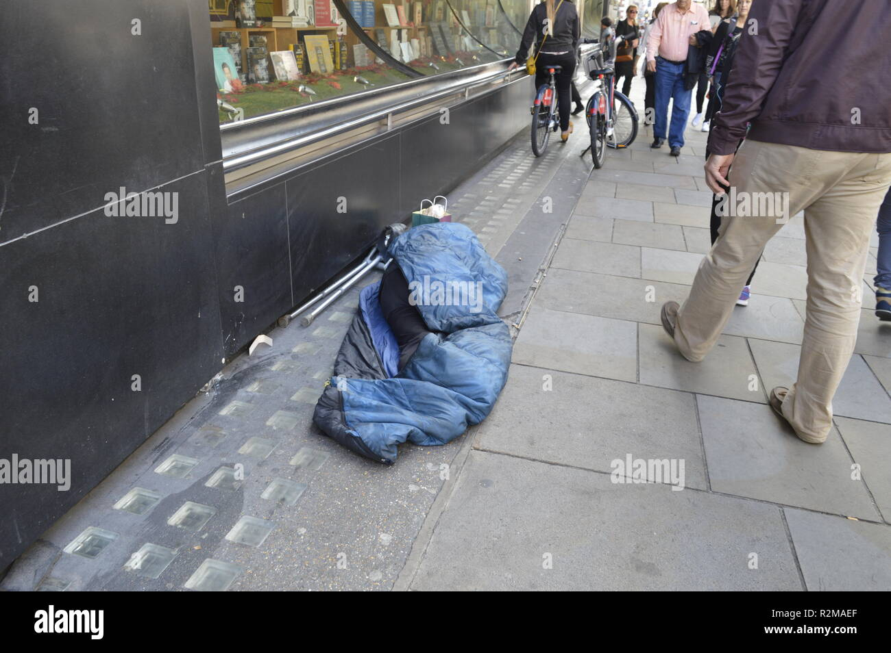 Homeless beggar asleep in a Piccadilly Street, London, UK. Itinerant workers come to England with little or no money for a bed for the night. - Stock Image