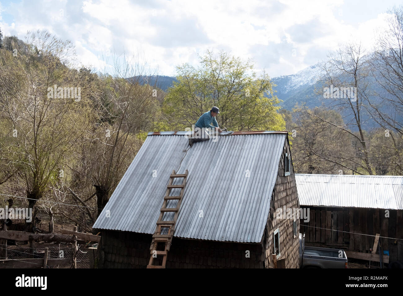 A member of the Mapuche tribal people, repairs the roof of his barn in Reigolil, Chile - Stock Image
