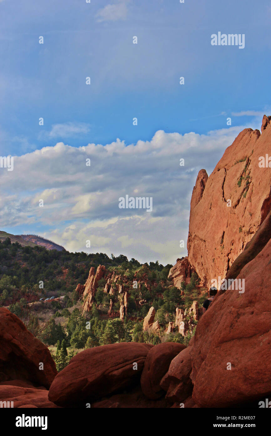 Sweeping landscape view of red rock pinnacles with pine covered mountains in the background while hiking at the Garden of the Gods in Colorado Springs - Stock Image