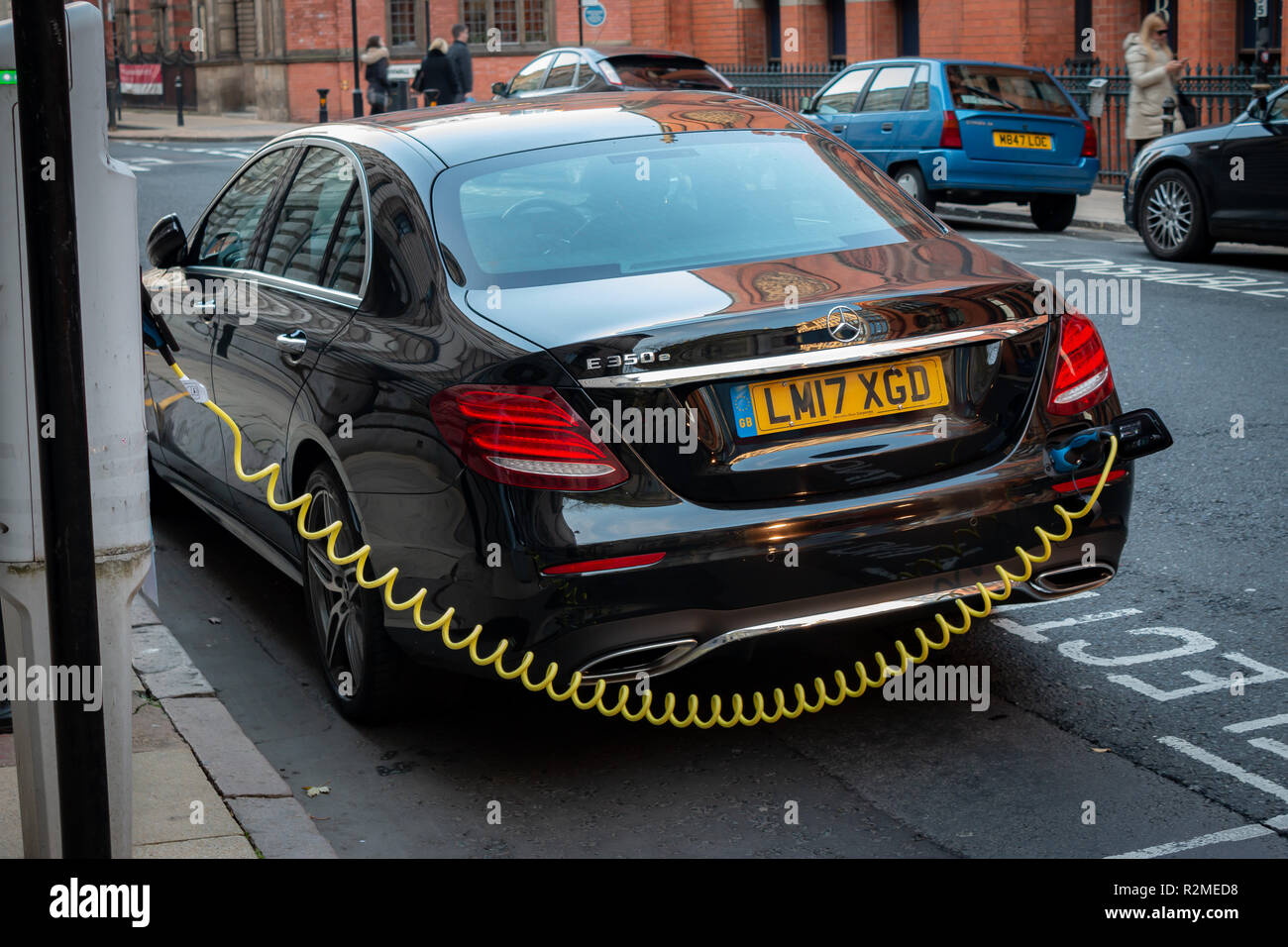 Modern electric Mercedes-Benz E Class vehicle being charged at an EV charging point. Stock Photo