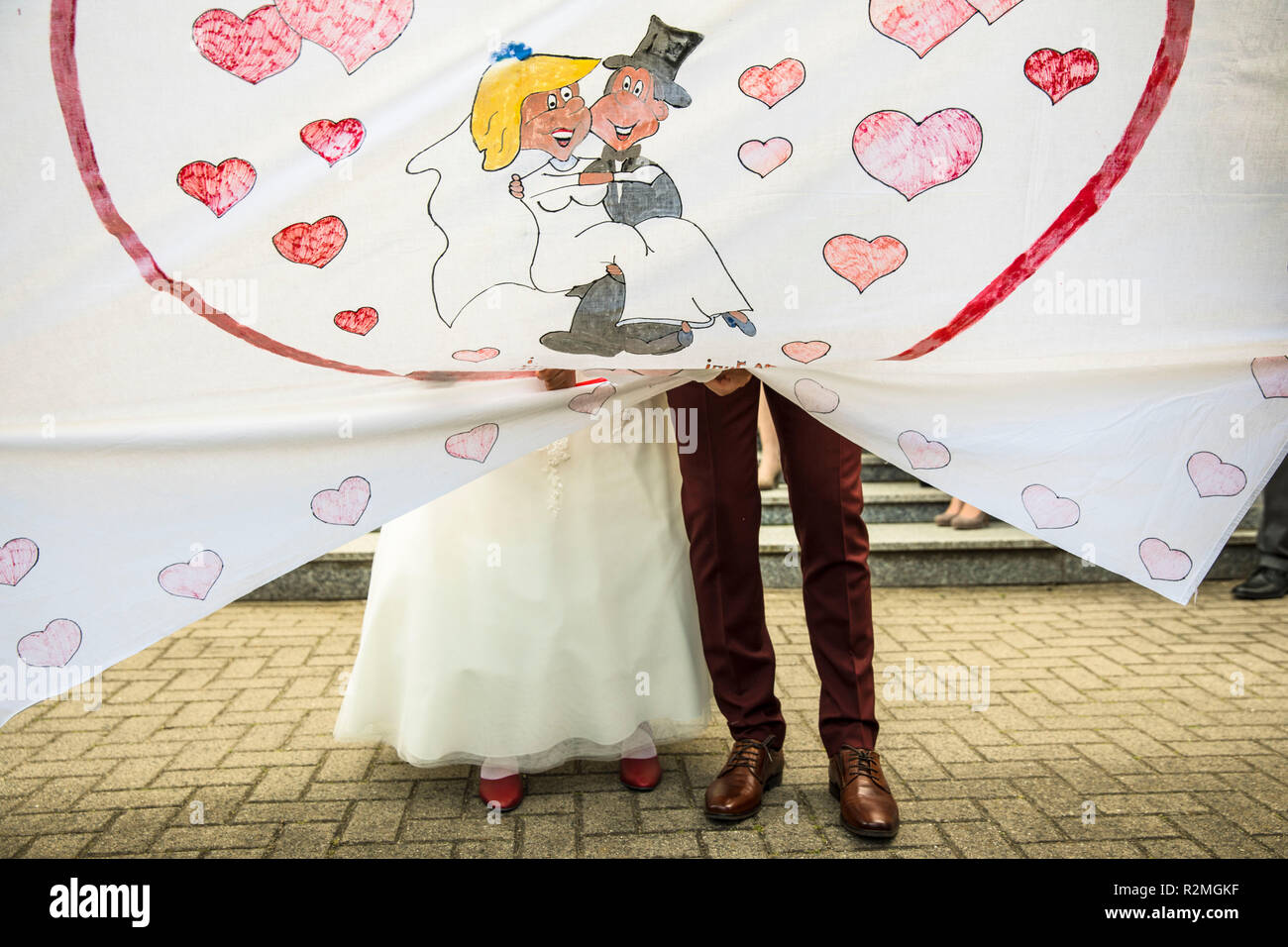 Wedding, couple cutting heart from painted sheet - Stock Image