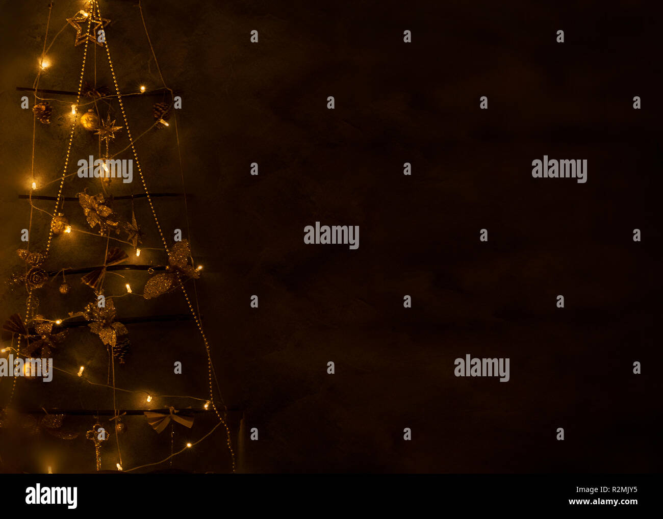 Christmas symbolic tree of bright lights, decorations, toys blank for greeting cards, place for text, in brown tones - Stock Image