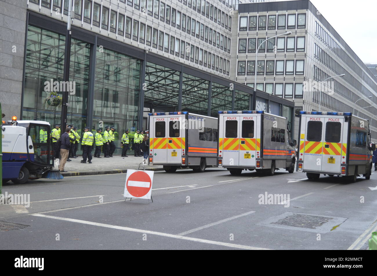 Police vehicles lined up to block the road, near Westminster, during student protest of 2015. Police teams guard the business center. London,UK. - Stock Image