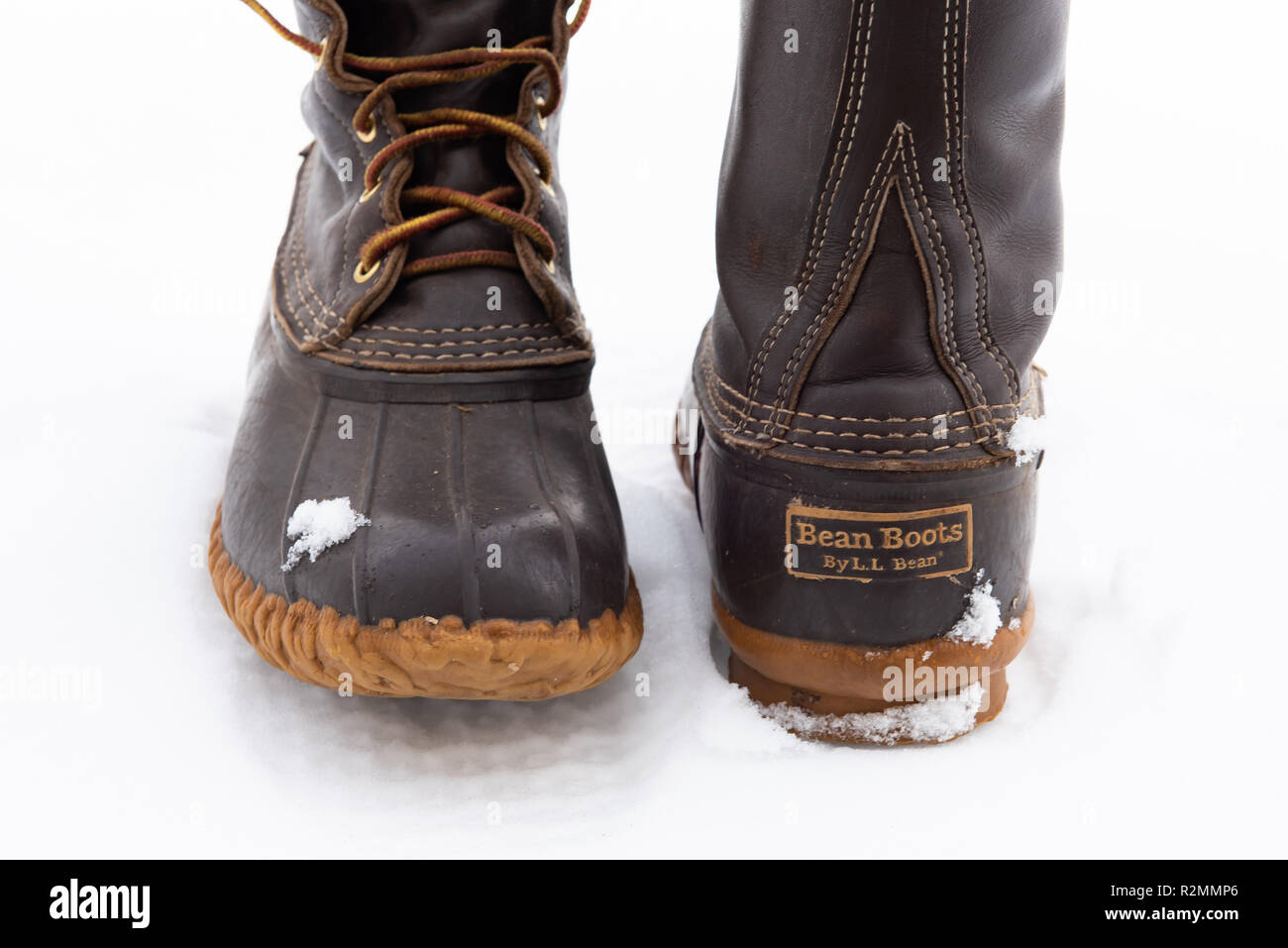 A pair of worn LL Bean boots in the snow, showing the leather and rubber construction and the distinctive chain link tread design and waterproof sole. - Stock Image