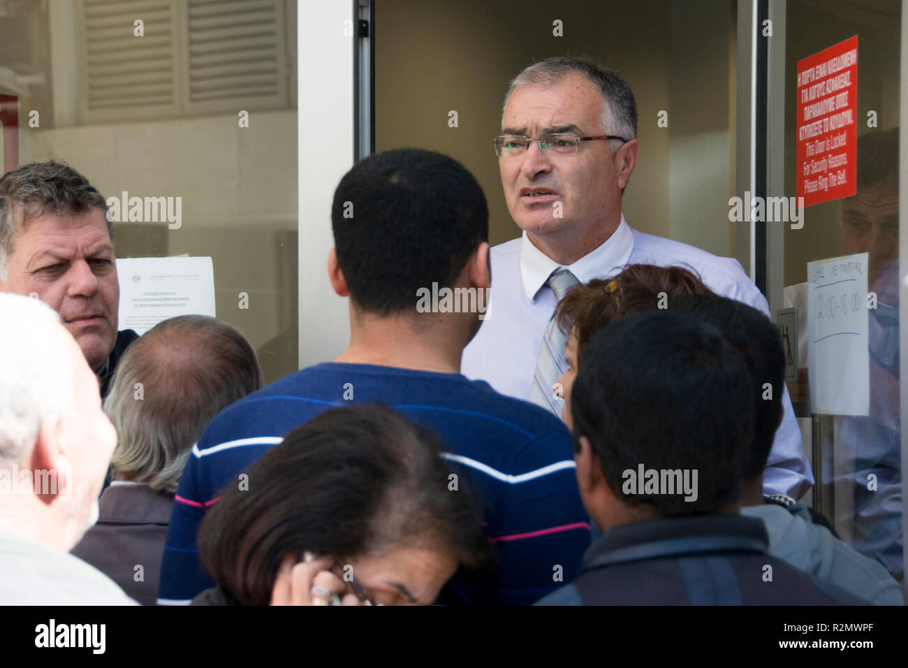 Nicosia, Cyprus 2013. Concerned bank manager addresses concerned crowd of customers moments after bank opens for the first time in weeks - Stock Image