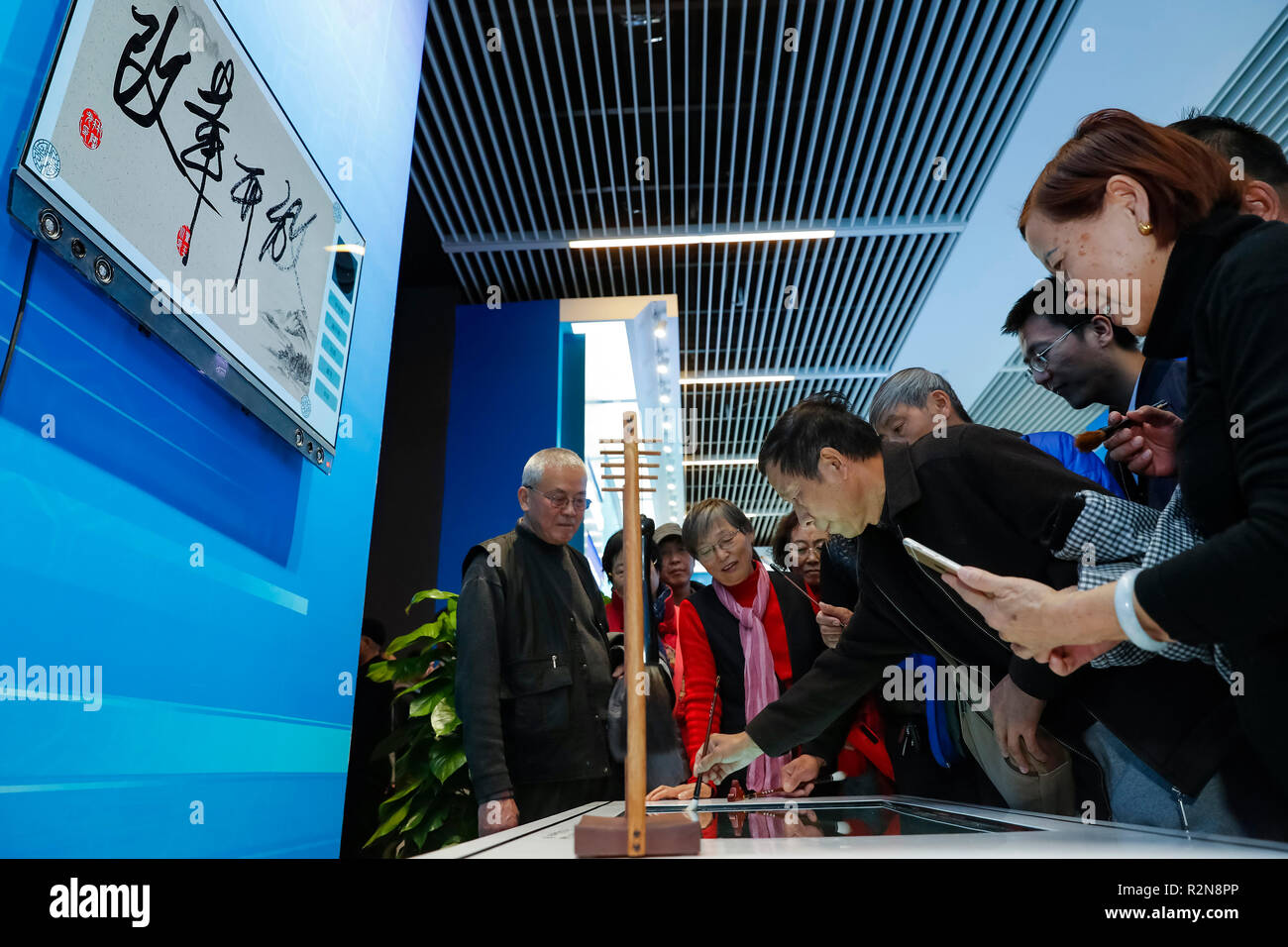 Beijing, China. 20th Nov, 2018. The 64-year-old Huang Chengchu from central China's Hunan Province experience an intelligent calligraphy exhibit during a major exhibition to commemorate the 40th anniversary of China's reform and opening-up at the National Museum of China in Beijing, capital of China, Nov. 20, 2018. Credit: Shen Bohan/Xinhua/Alamy Live News - Stock Image