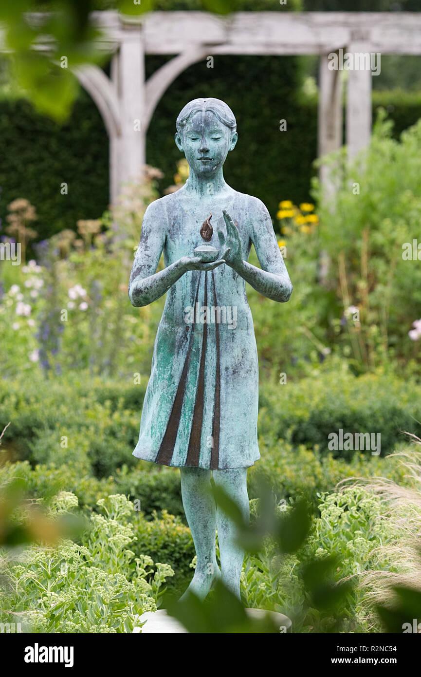 Girl statue  'lamp of wisdom'. Waterperry gardens, ornamental garden statue. - Stock Image
