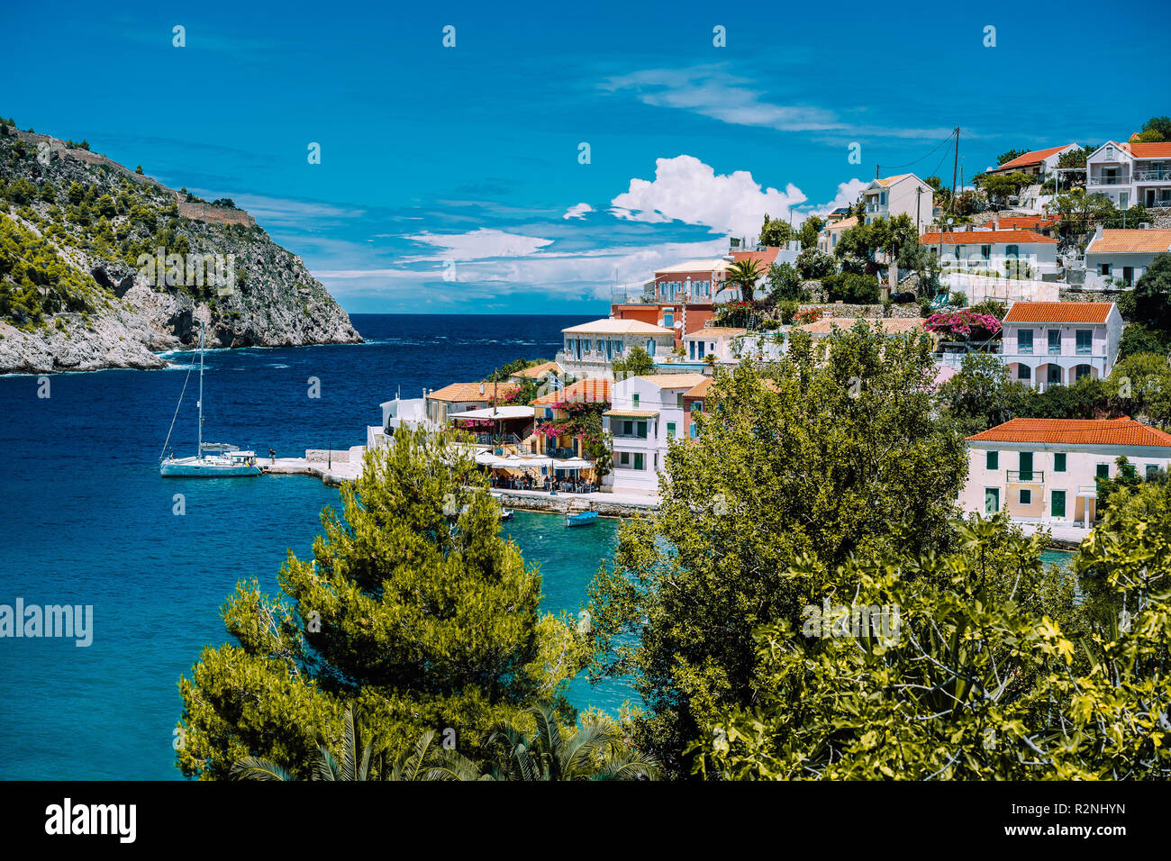 Assos village. Beautiful view to vivid colorful houses near blue turquoise colored transparent bay lagoon with yacht ship. Kefalonia, Greece - Stock Image