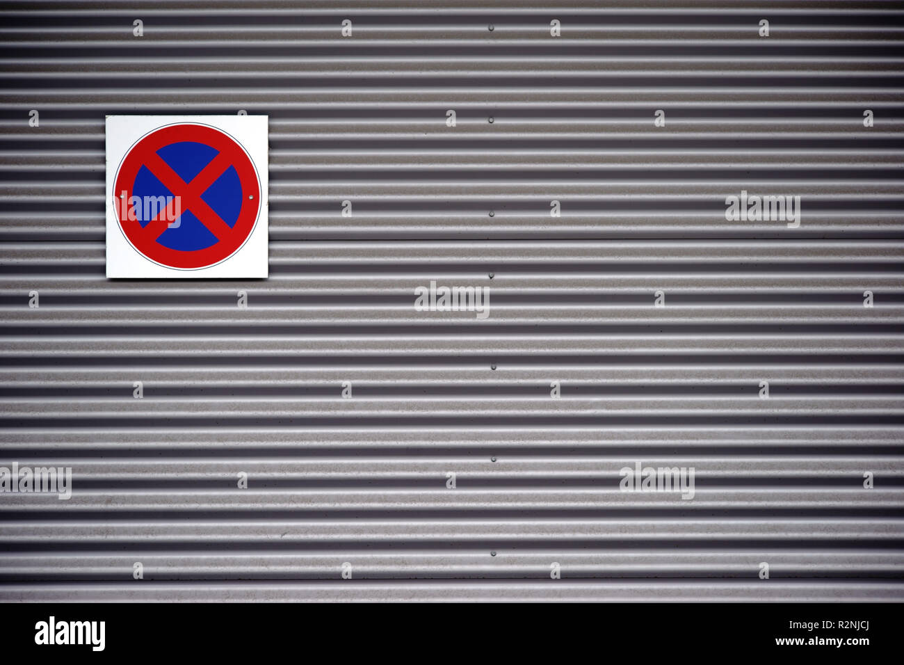A no-stop sign screwed to a corrugated iron facade, - Stock Image