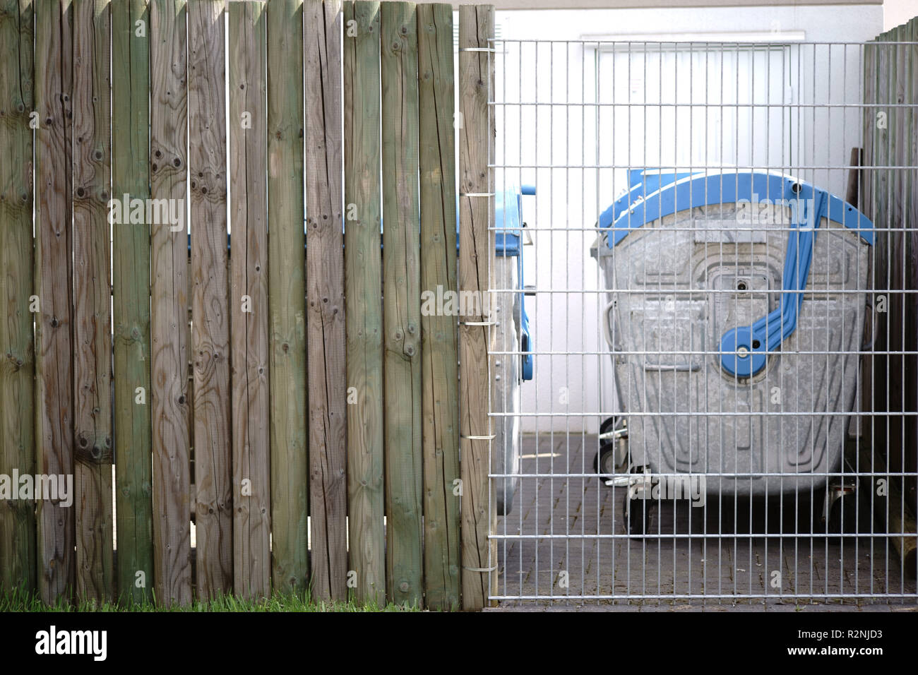 Trashcans arranged in a row stand behind a mesh fence in a closed off area, - Stock Image